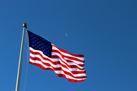 An American Flag Isolated on Blue Sky with Quarter Moon Peeking